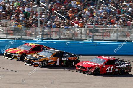 Kyle Larson (42), Kurt Busch (1) and Cole Custer (41) race three wide through Turn 4 during the NASCAR Cup Series auto race at Phoenix Raceway, in Avondale, Ariz