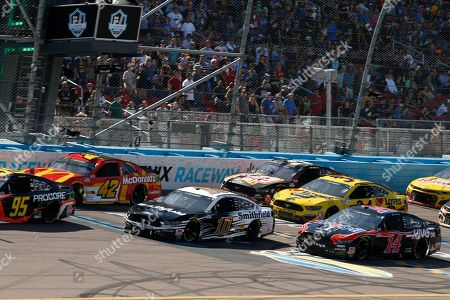 Kyle Larson (42), Aric Almirola (10) and Clint Bowyer (14) race others past the start/finish line during the NASCAR Cup Series auto race at Phoenix Raceway, in Avondale, Ariz