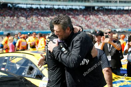 Stock Image of Country music singer and television personality Blake Shelton, right, embraces driver Jimmie Johnson prior to a NASCAR Cup Series auto race at Phoenix Raceway, in Avondale, Ariz