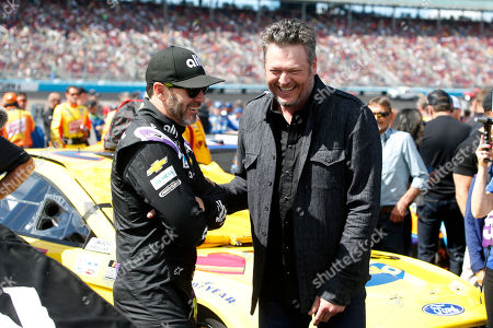 Country music singer and television personality Blake Shelton, right, jokes with driver Jimmie Johnson prior to a NASCAR Cup Series auto race at Phoenix Raceway, in Avondale, Ariz