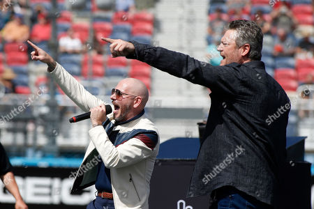 Singer, songwriter Pitbull, left, and country music singer and television personality Blake Shelton perform prior to a NASCAR Cup Series auto race at Phoenix Raceway, in Avondale, Ariz