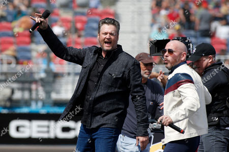 Country music singer and television personality Blake Shelton, left, and singer, songwriter Pitbull perform prior to a NASCAR Cup Series auto race at Phoenix Raceway, in Avondale, Ariz