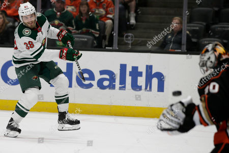 Minnesota Wild right wing Ryan Hartman, left, takes a slapshot at Anaheim Ducks goaltender Ryan Miller, right, during the first period of an NHL hockey game in Anaheim, Calif