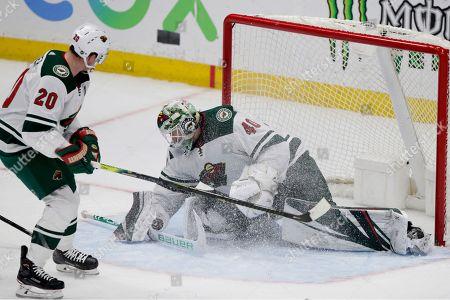 Minnesota Wild goaltender Devan Dubnyk (40) blocks a shot with defenseman Ryan Suter (20) watching during the third period of an NHL hockey game against the Anaheim Ducks in Anaheim, Calif