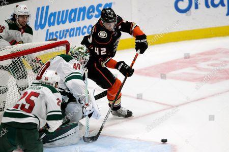 Anaheim Ducks defenseman Josh Manson, right, battles Minnesota Wild goaltender Devan Dubnyk, center, for the puck with right wing Mats Zuccarello, top left, of Norway, and defenseman Jonas Brodin (25), of Sweden, watching during the third period of an NHL hockey game in Anaheim, Calif