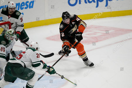 Stock Image of Anaheim Ducks defenseman Josh Manson, right, battles Minnesota Wild goaltender Devan Dubnyk, left, for the puck with right wing Mats Zuccarello, top left, of Norway, and defenseman Jonas Brodin (25), of Sweden, during the third period of an NHL hockey game in Anaheim, Calif