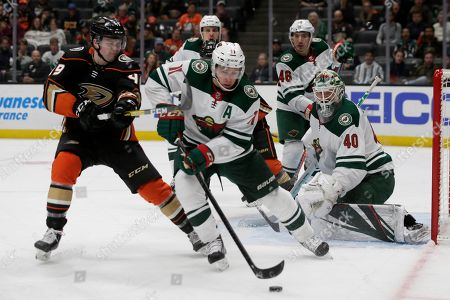 Minnesota Wild left wing Zach Parise, center, controls the puck under pressure by Anaheim Ducks left wing Max Jones, left, with goaltender Devan Dubnyk, right, watching during the second period of an NHL hockey game in Anaheim, Calif