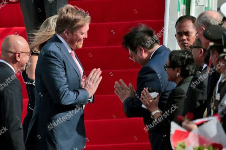 King Willem-Alexander of the Netherlands, center left, performs namaste greeting as he is introduced to Indonesian Foreign Minister Retno Marsudi, center right front, and Coordinating Minister for Economic Affairs Airlangga Hartarto, rear center right, upon arrival at Halim Perdanakusuma International Airport in Jakarta, Indonesia, . The Dutch royal couple are currently on on a five-day visit in the country