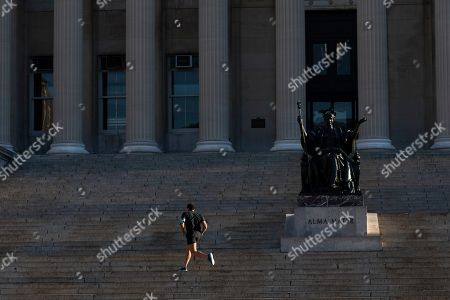 A man jogs in front of Low Library on the Columbia University campus, in New York. The Ivy League school is canceling two days of classes this week because a person at the New York school is under quarantine from the rapidly spreading coronavirus, according to university president Lee Bollinger