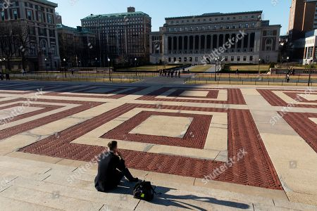 A man sits on the Columbia University campus, in New York. The Ivy League school is canceling two days of classes this week because a person at the New York school is under quarantine from the rapidly spreading coronavirus, according to university president Lee Bollinger