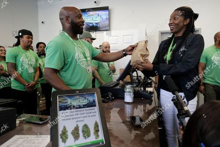 Kevin Hart, front left, co-owner of Pure Oasis recreational marijuana shop, completes a sale of cannabis products to the stores first customer Niambe McIntosh, front right, moments after the store opened for the first time, in Boston. Pure Oasis is Boston's first recreational marijuana shop, and the state's first black-owned one