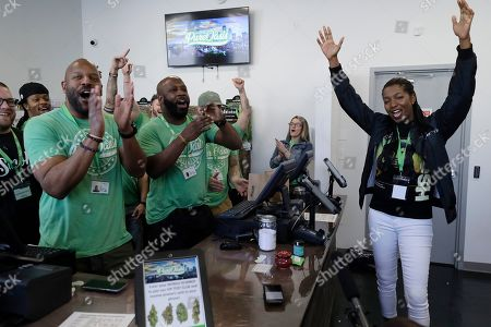 Stock Picture of Entrepreneurs Kobie Evans, front left, and Kevin Hart, center left, celebrate the opening of Pure Oasis recreational marijuana shop with their first customer Niambe McIntosh, right, the moment the shop opened for the first time, in Boston. Pure Oasis is Boston's first recreational marijuana shop, and the state's first black-owned one