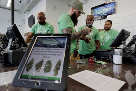 Entrepreneurs Kobie Evans, left, and Kevin Hart, second from right, work with retail sales manager Patrick Hoy, center front, moments before Pure Oasis recreational marijuana shop opened for the first time, in Boston. Pure Oasis is Boston's first recreational marijuana shop, and the state's first black-owned one. Evans and Hart are co-owners of the shop