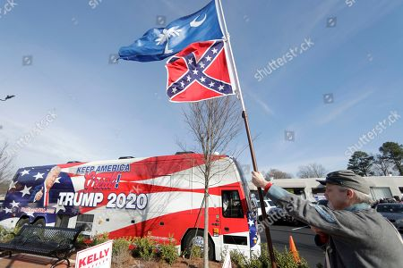 Civil War reenactor Billy Beardon holds a confederate battle flag and South Carolina state flag outside an appearance by former U.N. Ambassador and South Carolina Governor Nikki Haley at a campaign rally for Sen. Kelly Loeffler, R-Ga., in Marietta, Ga. While governor Haley signed legislation that removed the battle flag from the South Carolina Statehouse grounds