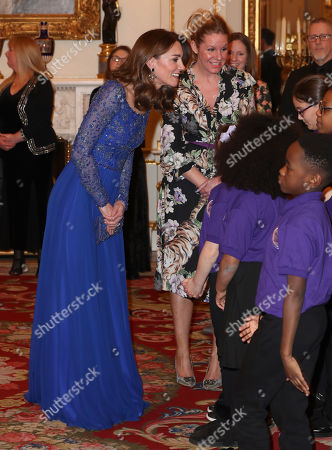 Stock Photo of Catherine Duchess of Cambridge speaks with a school choir as she hosts a Gala Dinner in celebration of the 25th anniversary of Place2Be at Buckingham Palace.