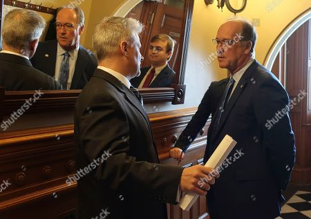 Senate Vice President Jeff Longbine, R-Emporia, right, speaks with Tim Graham, left, a member of Democratic Gov. Laura Kelly's staff, outside the Senate chamber, at the Statehouse in Topeka, Kan. Pictured in the center in the mirror is Michael Murray, Longbine's chief of staff. A new legislative proposal would increase the budgets of legislative leaders' offices, with the biggest increases going to Longbine's office and the House speaker pro tem's office
