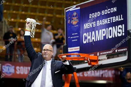 East Tennessee State head coach Steve Forbes waves the net in the air after cutting it from the rim to celebrate his team's over Wofford for the NCAA men's college basketball championship for the Southern Conference tournament, in Asheville, N.C