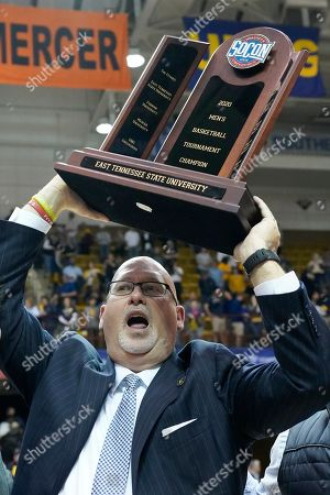 East Tennessee State head coach Steve Forbes raises the NCAA men's basketball Southern Conference tournament championship trophy after his team defeated Wofford, in Asheville, N.C