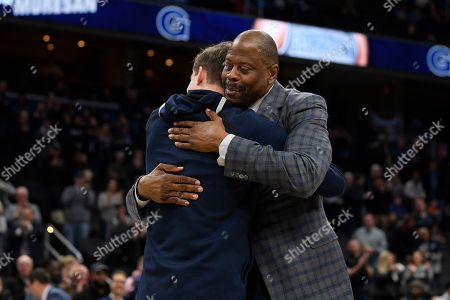 Georgetown head coach Patrick Ewing, right, reacts with forward George Muresan (20) during senior day festivities before an NCAA college basketball game against Villanova, in Washington