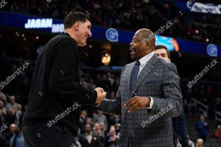 Georgetown head coach Patrick Ewing, right, reacts with forward George Muresan, back obscured, and his father Gheorghe Muresan, left, during senior day festivities before an NCAA college basketball game against Villanova, in Washington