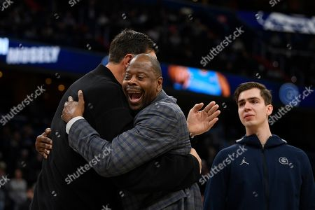 Georgetown head coach Patrick Ewing, center, reacts with forward George Muresan, right, and his father Gheorghe Muresan, left, during senior day festivities before an NCAA college basketball game against Villanova, in Washington