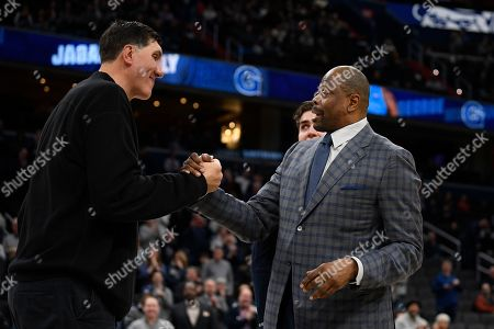 Georgetown head coach Patrick Ewing, right, reacts with forward George Muresan, center back, and his father Gheorghe Muresan, left, during senior day festivities before an NCAA college basketball game against Villanova, in Washington