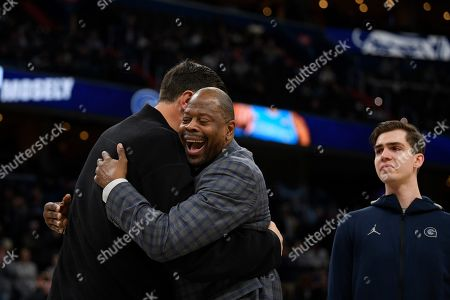 Stock Photo of Georgetown head coach Patrick Ewing, center, reacts with forward George Muresan, right, and his father Gheorghe Muresan, left, during senior day festivities before an NCAA college basketball game against Villanova, in Washington