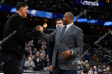 Georgetown head coach Patrick Ewing, right, reacts with forward George Muresan, center, and his father Gheorghe Muresan, left, during senior day festivities before an NCAA college basketball game against Villanova, in Washington