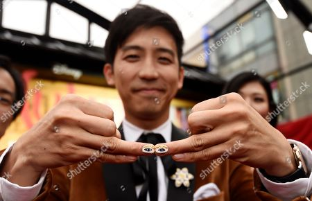 """Jimmy Wong, a cast member in the new live-action """"Mulan,"""" shows off his fingernails to photographers at the premiere of the film at the El Capitan Theatre, in Los Angeles"""