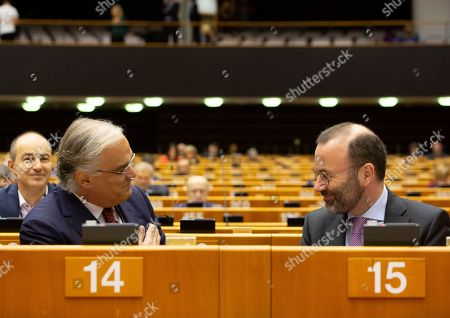German MEP Manfred Weber, right, attends a session in the Plenary chamber of the European Parliament in Brussels, . EU lawmakers were due to take part in a drastically shortened European parliamentary session in Brussels amid concern about the spread of coronavirus. EU leaders were also due to hold a videoconference Tuesday to coordinate efforts across the 27-nation bloc to slow the disease down
