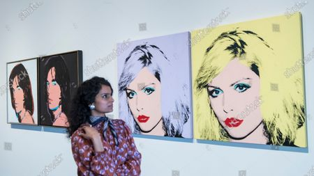"""A staff member poses next to (L to R) """"Mick Jagger"""", and """"Debbie Harry"""", 1980, both by Andy Warhol."""