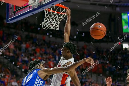 Stock Photo of Keion Brooks Jr., Omar Payne. Kentucky forward Keion Brooks Jr. (12) blocks the shot of Florida forward Omar Payne (5) during the first half of an NCAA college basketball game, in Gainesville, Fla