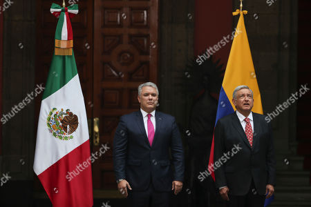 Mexico's President Manuel Andres Lopez Obrador, right, sings his country's national anthem during a welcoming ceremony for his Colombian counterpart Ivan Duque, at the National Palace in Mexico City