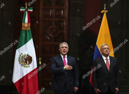 Colombia's President Ivan Duque, left, sings his country's national anthem standing next to Mexico's President Manuel Andres Lopez Obrador during a welcoming ceremony at the National Palace in Mexico City