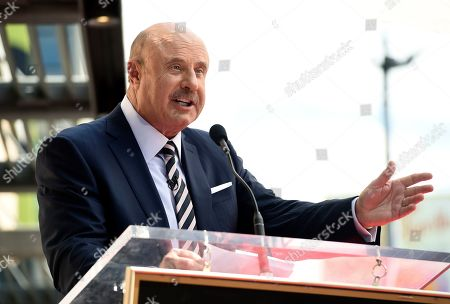 """Talk show host Dr. Phil McGraw speaking during a ceremony awarding him with a star on the Hollywood Walk of Fame in Los Angeles. The """"Dr. Phil"""" daytime talk show will tape without a studio audience for roughly two weeks as a precaution against the new coronavirus. The show typically tapes with an audience of about 300 people at Paramount Studios in Los Angeles. For most people, the new coronavirus causes only mild or moderate symptoms, such as fever and cough. For some, especially older adults and people with existing health problems, it can cause more severe illness, including pneumonia. The vast majority of people recover from the new virus. According to the World Health Organization, people with mild illness recover in about two weeks, while those with more severe illness may take three to six weeks to recover"""