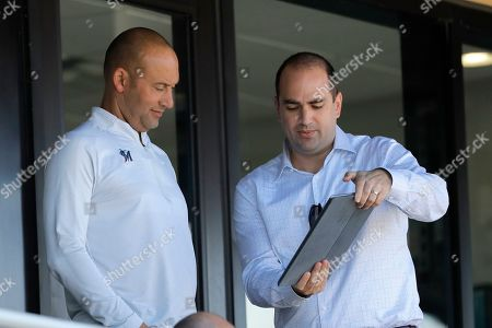 Miami Marlins CRO Adam Jones, right, shows a tablet to Marlins CEO Derek Jeter during the eighth inning of a spring training baseball game between the Washington Nationals and the Marlins, in Jupiter, Fla