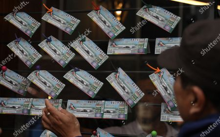 Stock Image of A man looks at a series of lottery tickets in Mexico City, Mexico, 10 March 2020. Six million tickets are on sale for the presidential plane raffle, which will be drawn on 15 September. The prize, 20 million pesos (1 million US dollars), is the approximate value of the Boeing 787 used by former Mexican President  Enrique Pena Nieto.
