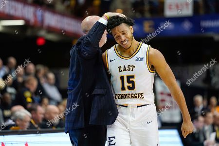 East Tennessee State head coach Steve Forbes pats guard Isaiah Tisdale on the head as he leaves the game near the end of the second half of an NCAA men's college basketball championship game for the Southern Conference tournament, in Asheville, N.C. East Tennessee St. defeated Wofford 72-58