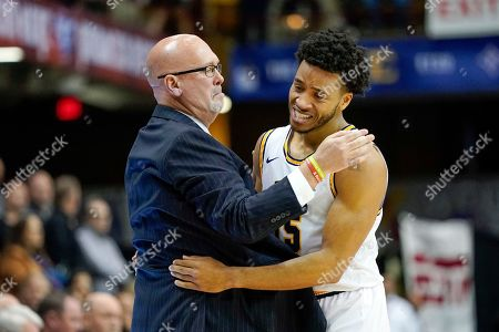 East Tennessee State head coach Steve Forbes is embraced by guard Isaiah Tisdale as he leaves the game near the end of the second half of an NCAA men's college basketball championship game for the Southern Conference tournament, in Asheville, N.C. East Tennessee St. defeated Wofford 72-58