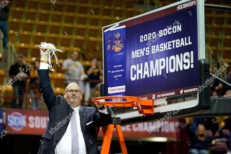 East Tennessee State head coach Steve Forbes waves the basketball net in the air after he cut the remaining piece off the rim to celebrate his team's 72-58 over Wofford for the NCAA men's college basketball championship for the Southern Conference tournament, in Asheville, N.C