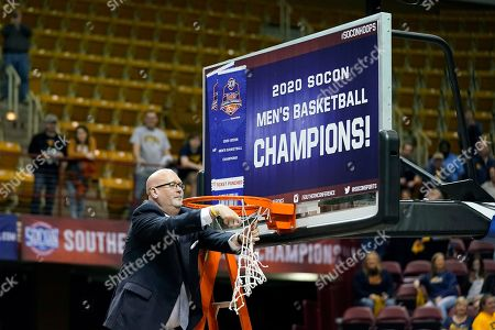 East Tennessee State head coach Steve Forbes cuts the basketball net off the rim to celebrate his team's 72-58 over Wofford for the NCAA men's college basketball championship for the Southern Conference tournament, in Asheville, N.C