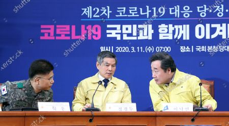 Lee Nak-yon (R), chief of the ruling Democratic Party's ad-hoc committee to fight the spread of the new coronavirus, talks with Defense Minister Jeong Kyeong-doo (C) and Medical Command chief Seok Woong during a ruling party-government-presidential office meeting at the National Assembly in Seoul, South Korea, on 11 March 2020, to discuss measures to contain the COVID-19 virus affecting South Korea.