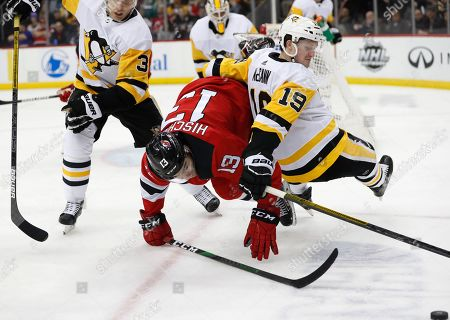 Stock Picture of Jared McCann, Nico Hischier, Jack Johnson. Pittsburgh Penguins center Jared McCann (19) falls over New Jersey Devils center Nico Hischier (13) as they try to get to the puck, lower right, with Penguins defenseman Jack Johnson (3) watching during the second period of an NHL hockey game, in Newark, N.J