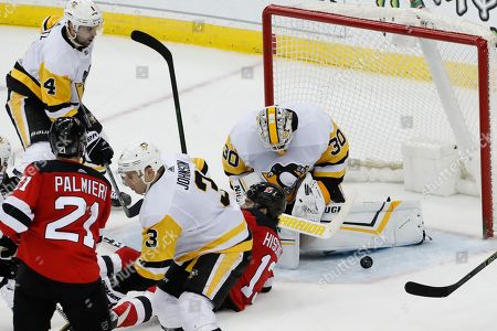 Matt Murray, Nico Hischier, Kyle Palmieri, Jack Johnson, Justin Schultz. Penguins goaltender Matt Murray (30) makes a save as New Jersey Devils center Nico Hischier (13) collides with him during the third period of an NHL hockey game, in Newark, N.J