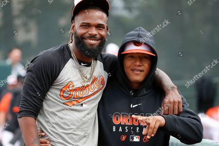 Baltimore Orioles pitcher Miguel Castro, left, hugs catcher Pedro Severino before a spring training baseball game against the Atlanta Braves, in Sarasota, Fla