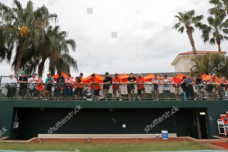 Fans watch overlooking the bullpen at Ed Smith Stadium before a spring training baseball game between the Baltimore Orioles and the Atlanta Braves, in Sarasota, Fla