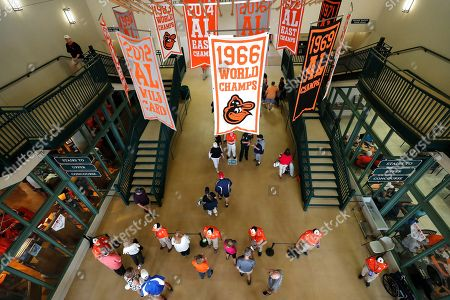 Fans make their way into Ed Smith Stadium for a spring training baseball game between the Baltimore Orioles and the Atlanta Braves, in Sarasota, Fla