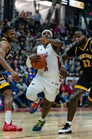 Braylon Rayson (middle) of Sudbury Five drives the ball through Randy Phillips (R) and Tyrell Green (L) of London Lightning