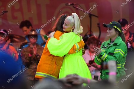US singer Katy Perry (C) hugs a Country Fire Authority (CFA) member during the 'FIGHT ON' concert for bushfire-affected communities at Pioneer Park Recreation Reserve in Bright, Victoria, Australia, 11 March 2020. The pop star is putting on a free show in Victoria's Alpine region.