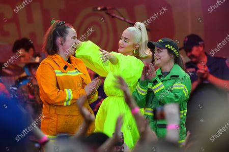 US singer Katy Perry (C) on stage with a CFA member and a Victorian Forest Fire Management employee during the 'FIGHT ON' concert for bushfire-affected communities at Pioneer Park Recreation Reserve in Bright, Victoria, Australia, 11 March 2020. The pop star is putting on a free show in Victoria's Alpine region.